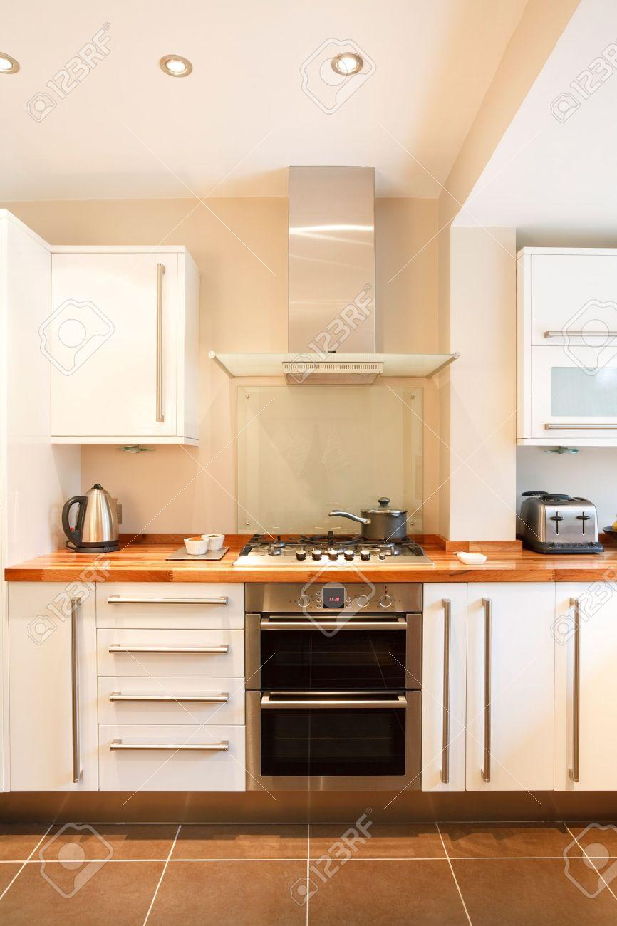 Modernt vitt kök med trä bänkskivor och rostfritt stål apparater ...