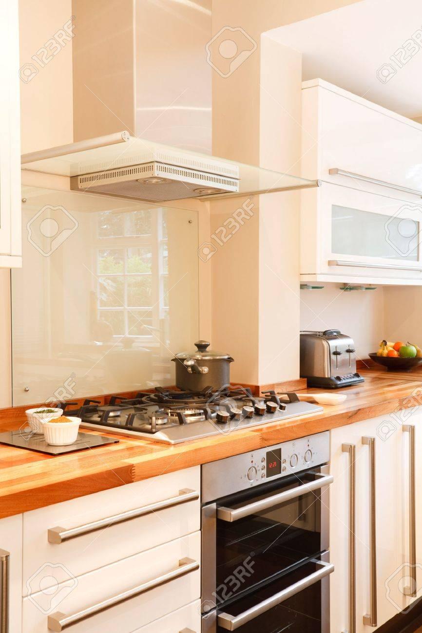 Moderne Weiße Küche Mit Edelstahl-Herd, Gasherd Und Kamin-Dunstabzug ...