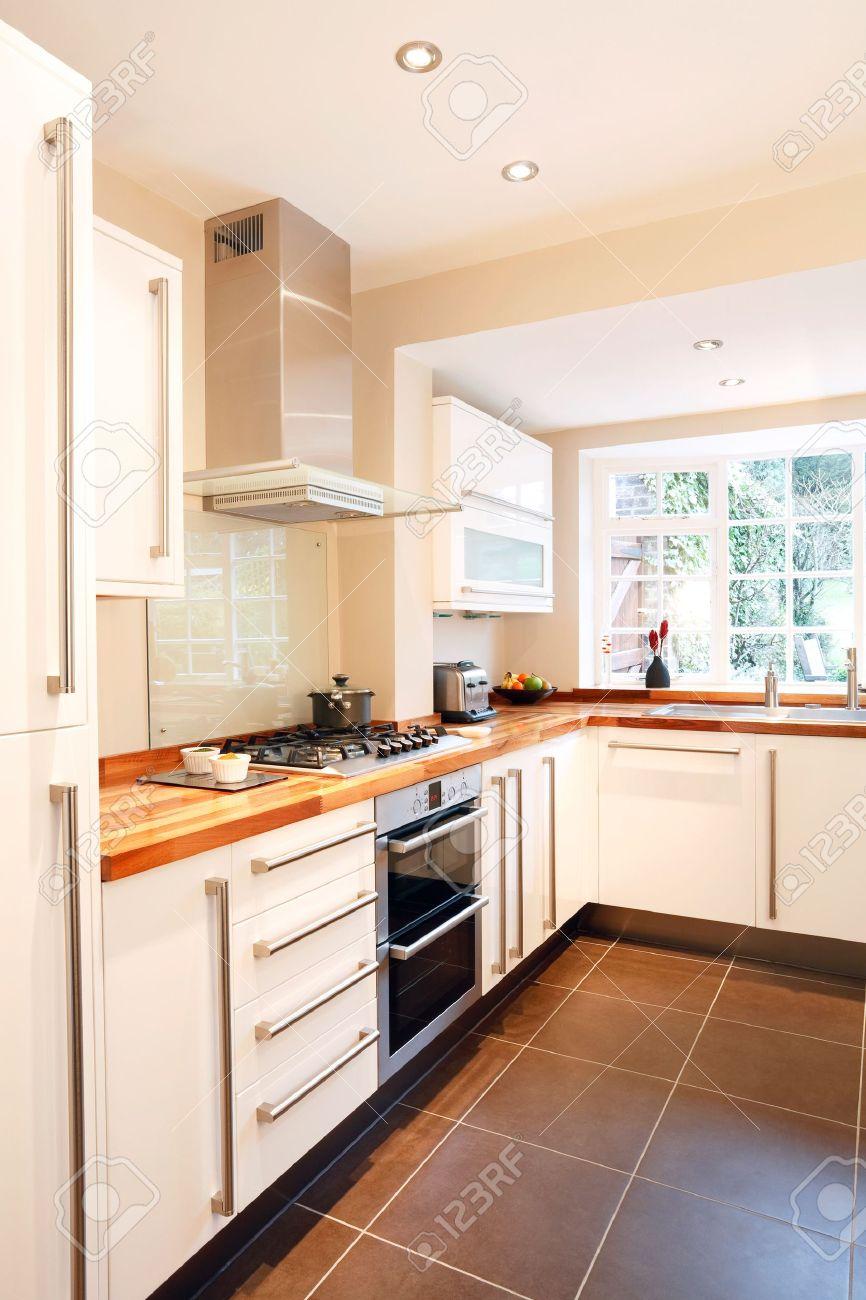 cocina blanca moderna con encimera de madera y de acero inoxidable foto de archivo