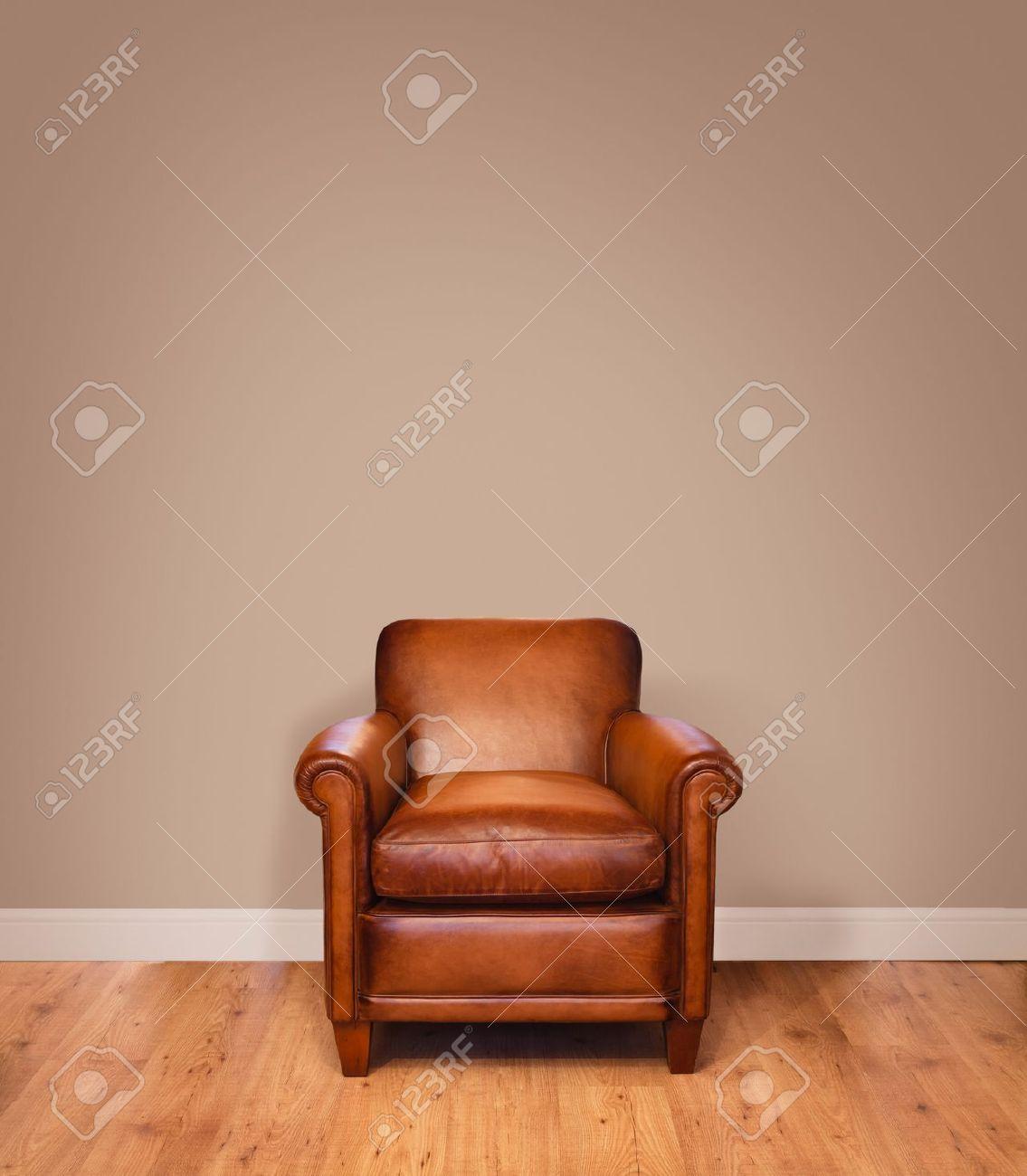Leather armchair on a wooden floor against a plain background ...