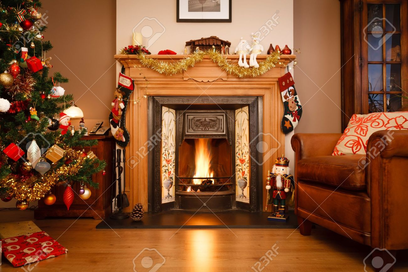 decorated fireplace in a family home with christmas tree stock