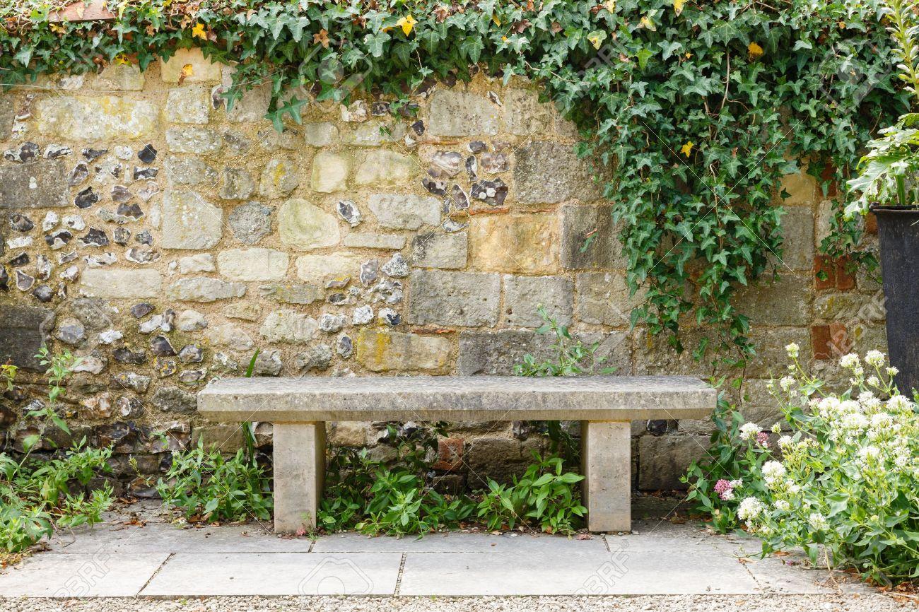 bench in einem formalen garten mit einer alten steinmauer, Garten Ideen