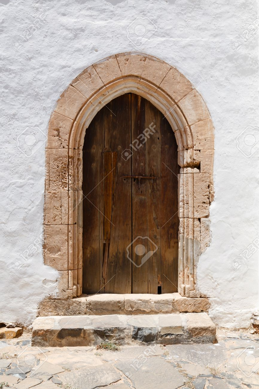 Ancient wooden arched door with stone archway and stucco white wall Stock Photo - 21494565 & Ancient Wooden Arched Door With Stone Archway And Stucco White ...