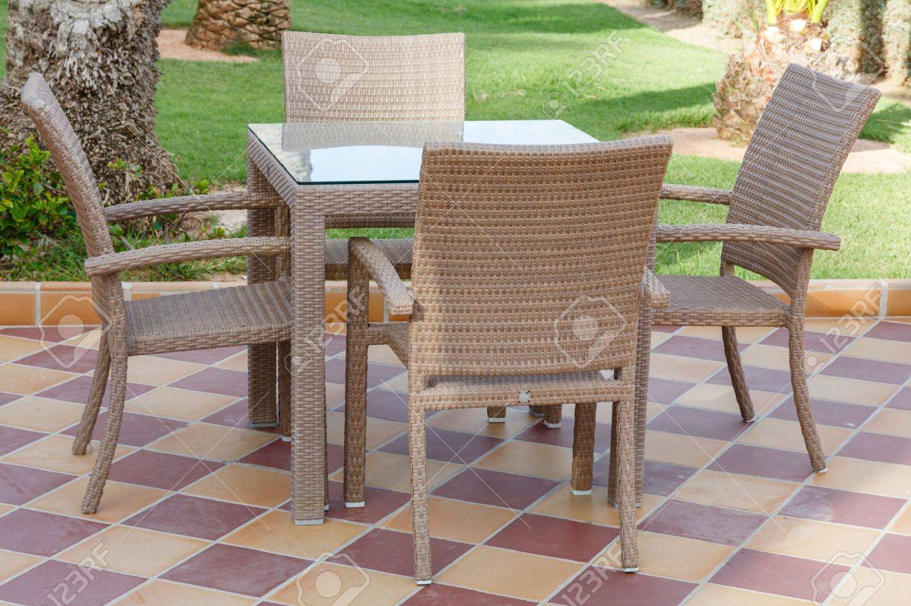Glass patio table and chairs - Cane Outdoor Patio Furniture With Glass Table And Chairs On Tiled Floor Stock Photo 21494566