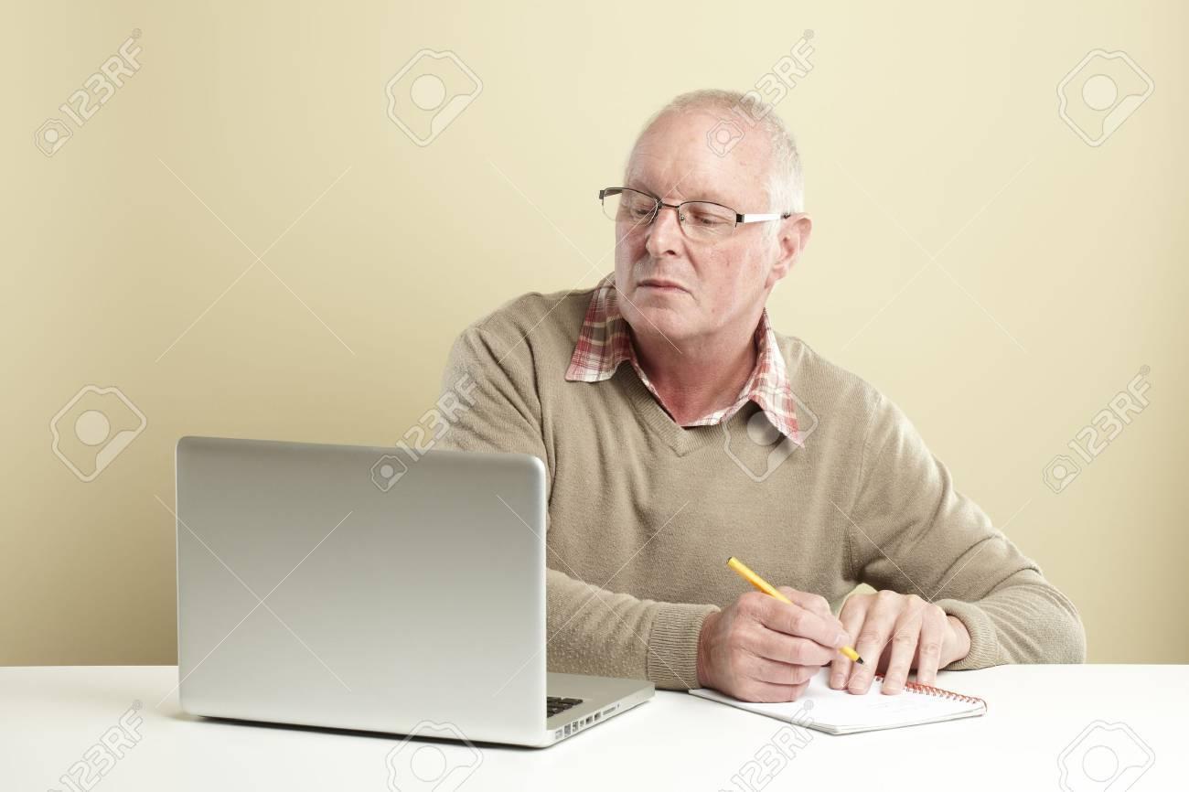 Senior man using laptop whilst taking notes Stock Photo - 14615946