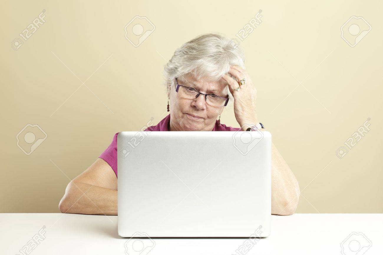 Senior woman using laptop whilst looking confused Stock Photo - 14615943