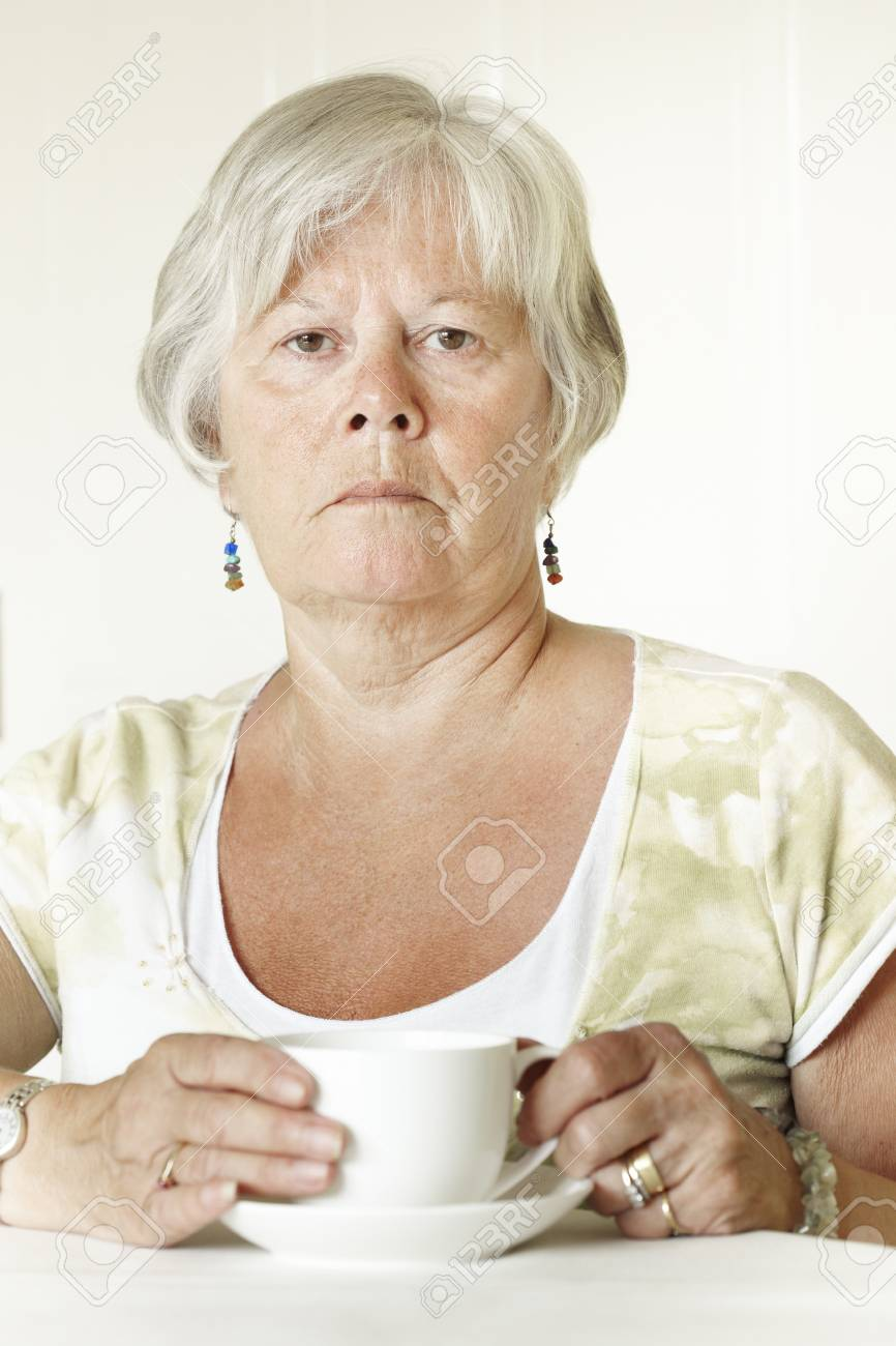 Thoughtful Senior lady sitting at table holding a cup of tea Stock Photo - 14652273