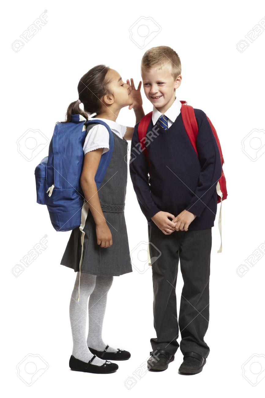 a62f0729ea 8 year old school girl with backpack whispering in boys ear smiling on white  background Stock