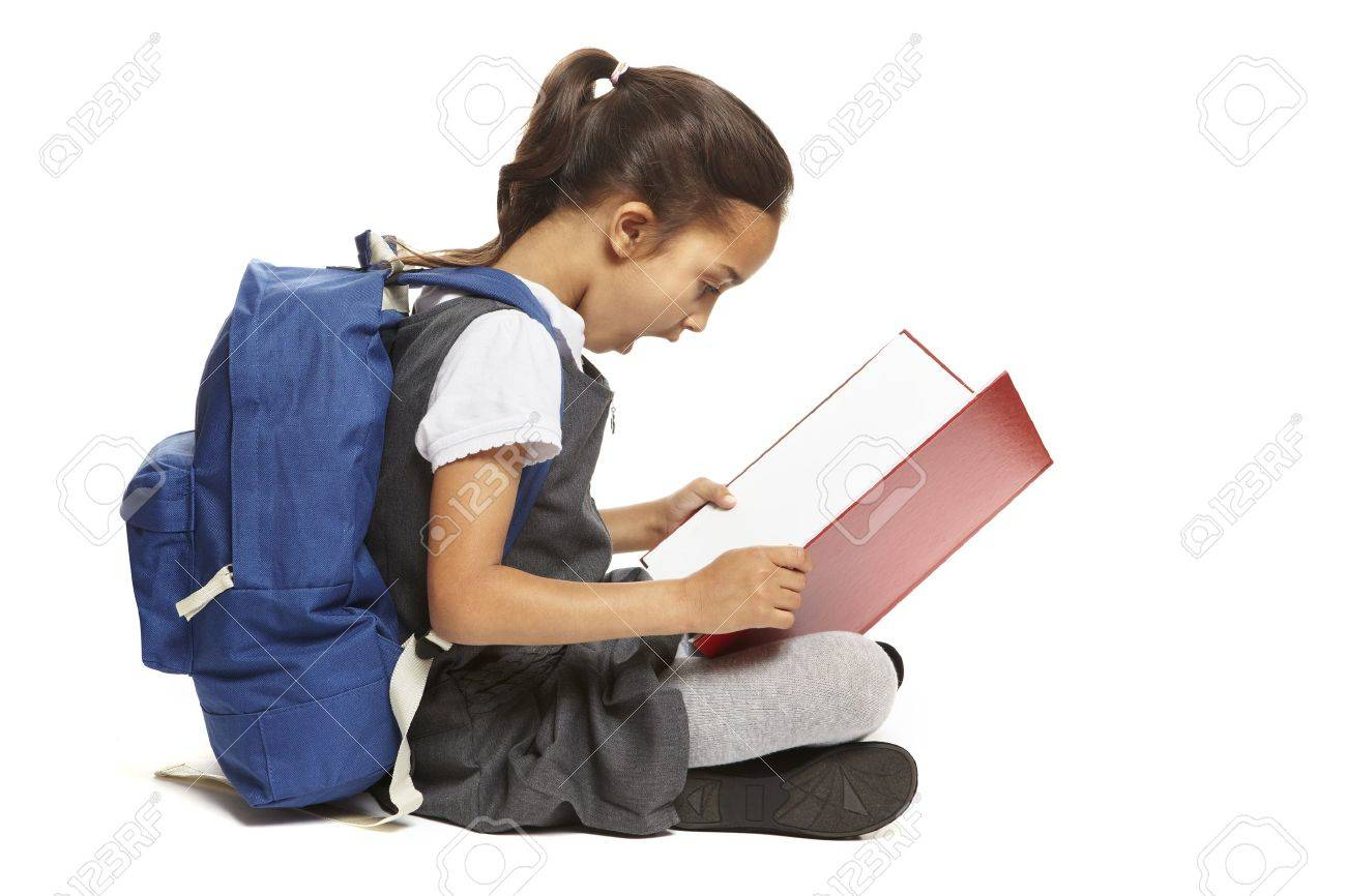 8 year old school girl sitting reading book with backpack looking shocked on white background Stock Photo - 14795500