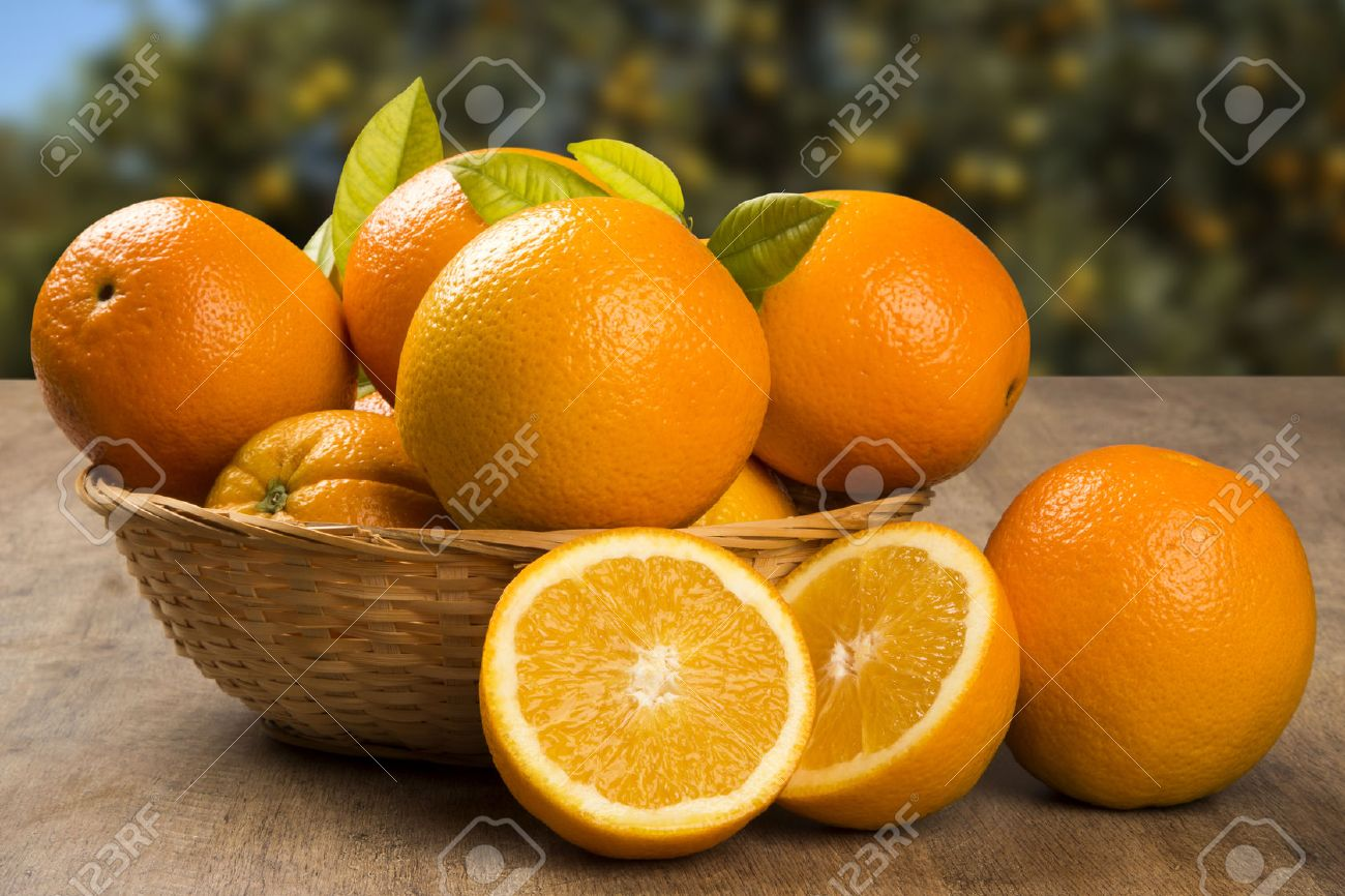 Close up of some oranges in a basket over a wooden surface. Fresh fruit. - 51223844