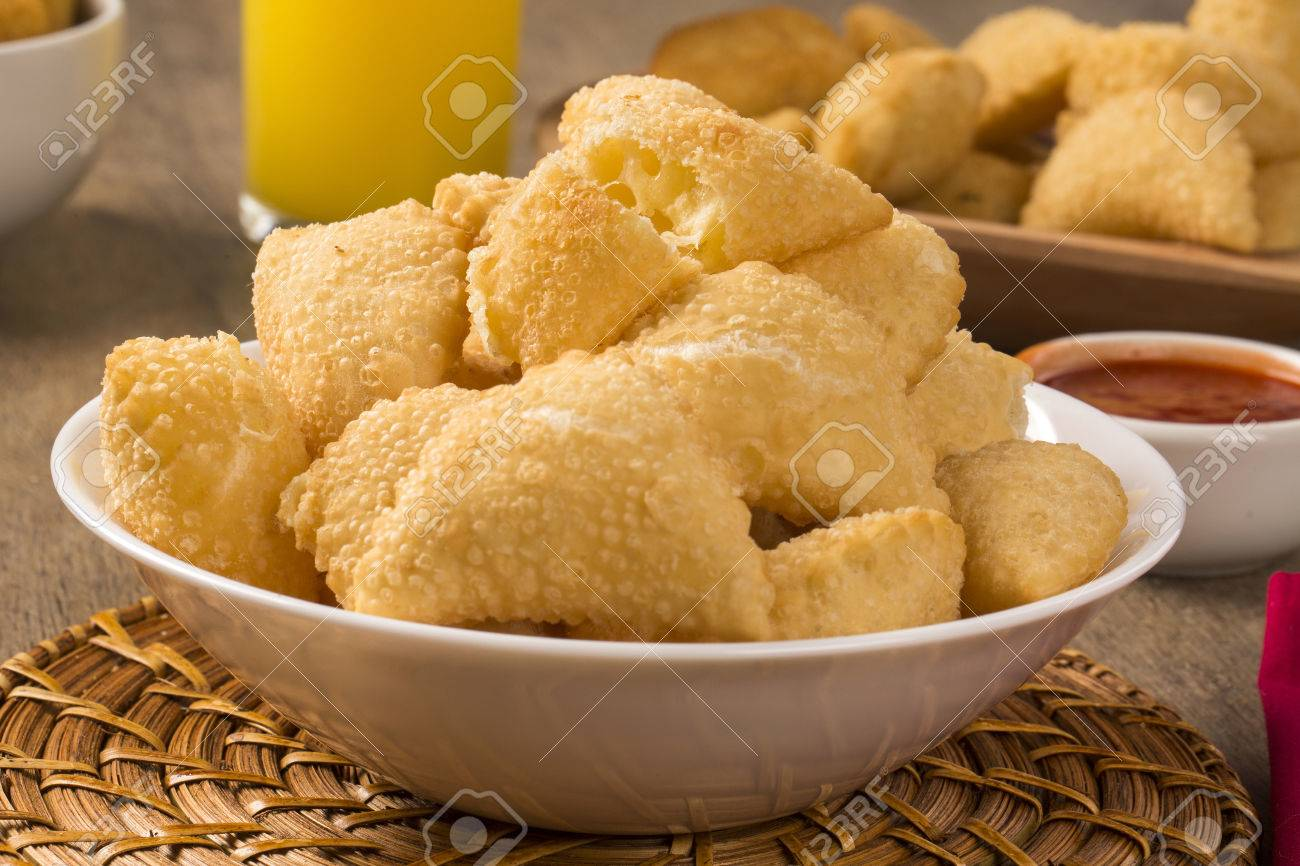 Pastel, a Brazilian snack, with a bar in the background. Cheese pastry on wooden background. - 52613035