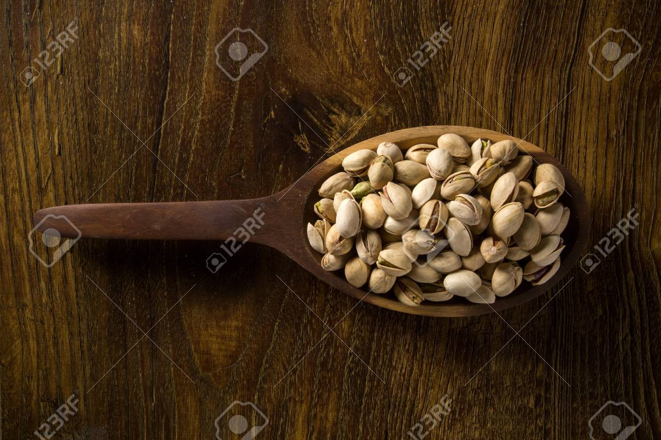 pistachio nuts in wood spoon on wood background - 78995240