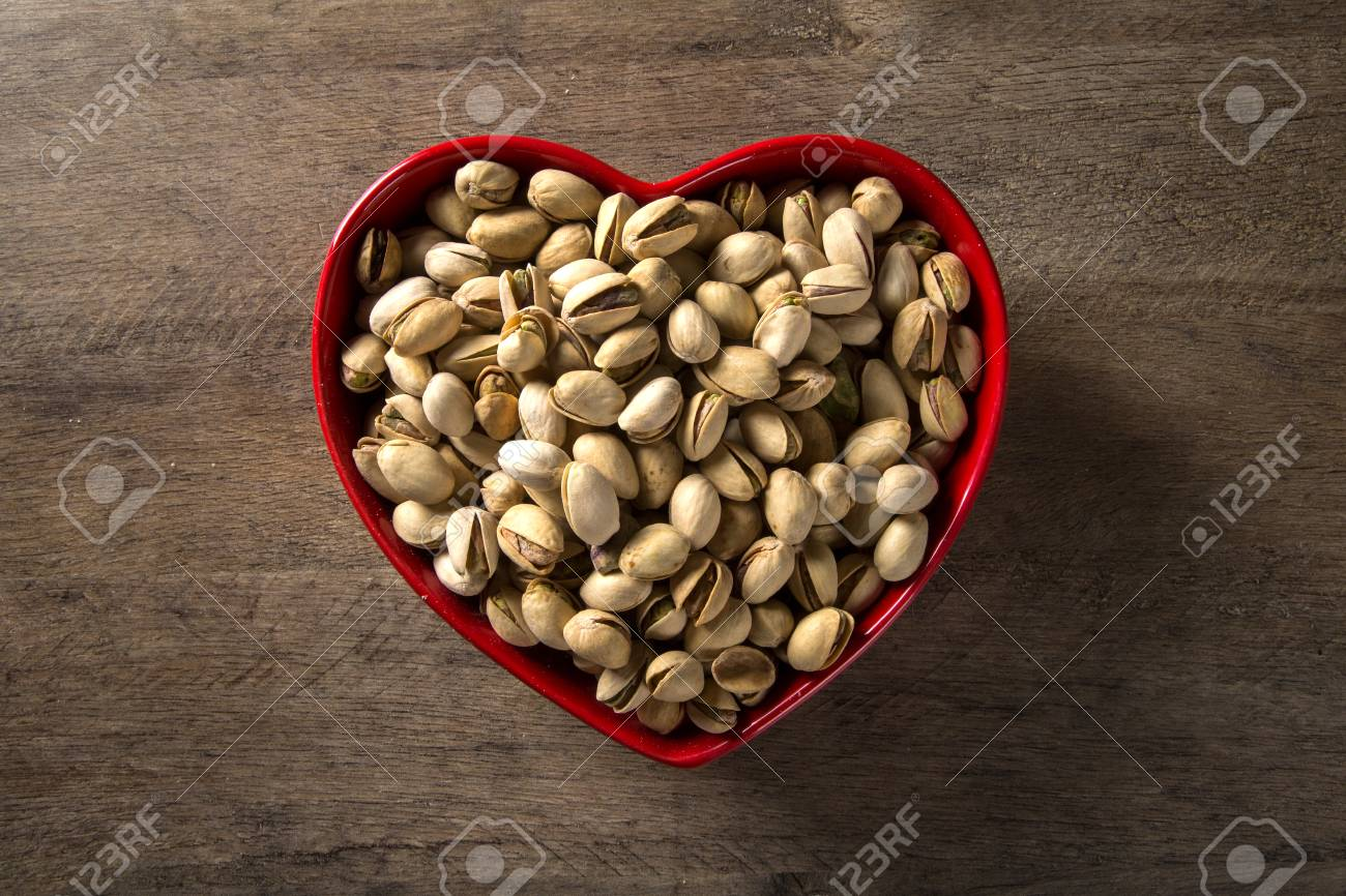 pistachio nuts in wood bowl with wood background. - 78995230