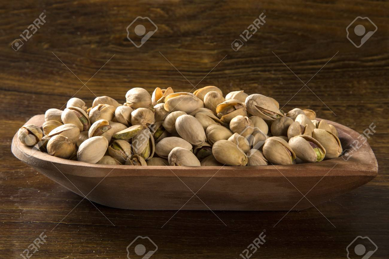 pistachio nuts in wood bowl with wood background. - 78949791
