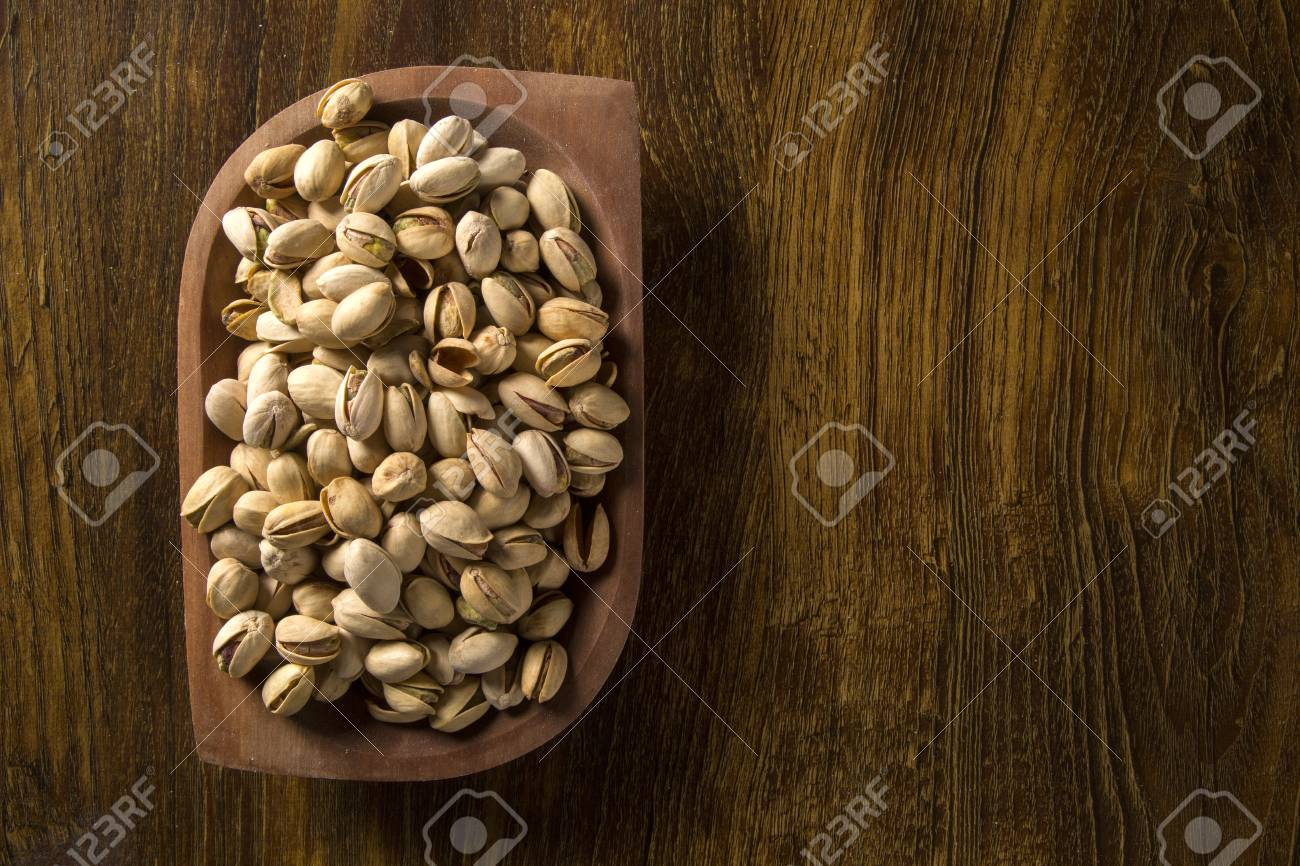 pistachio nuts in wood bowl with wood background. - 78936931