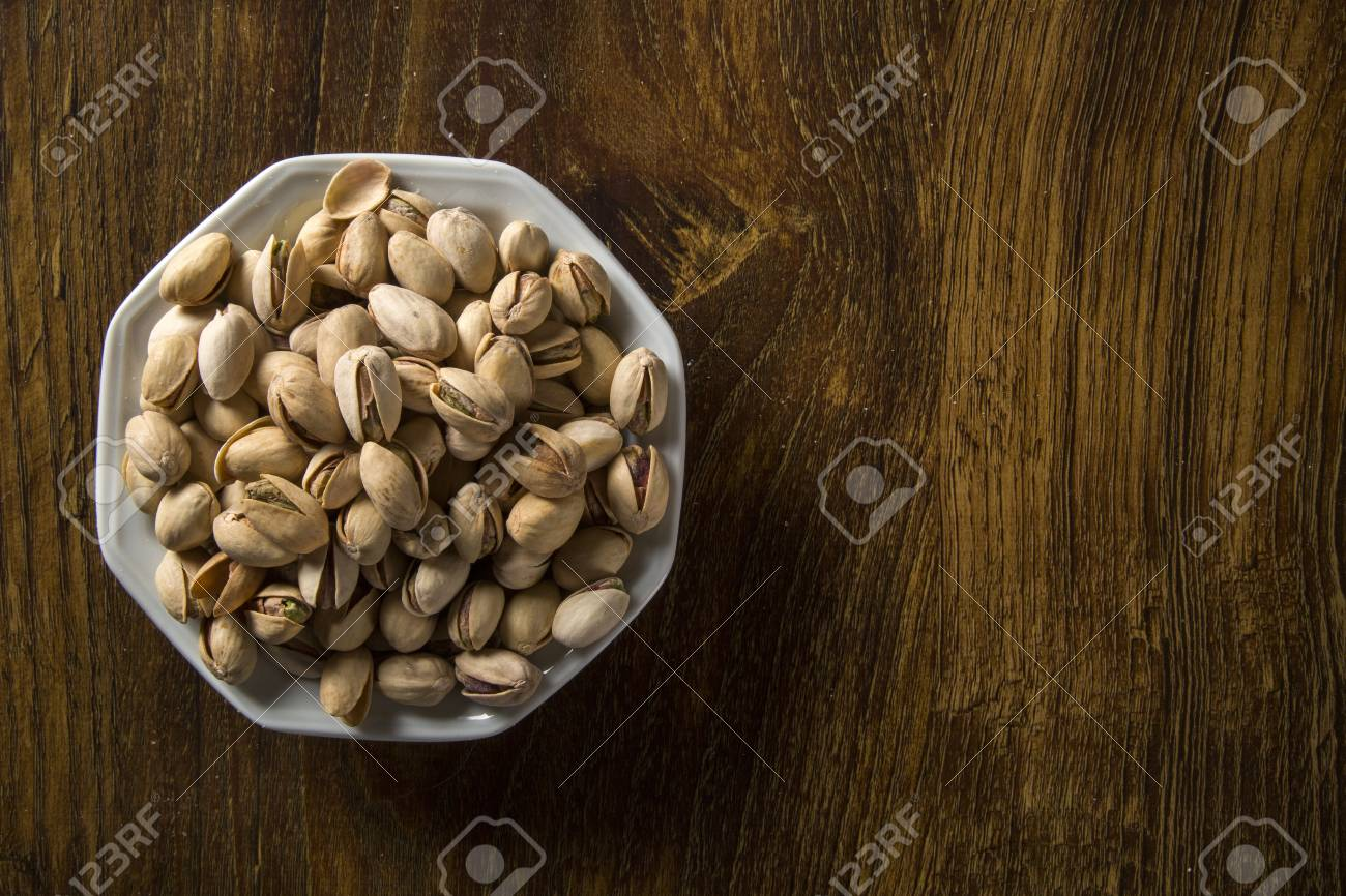pistachio nuts in white bowl with wood background. - 78949829