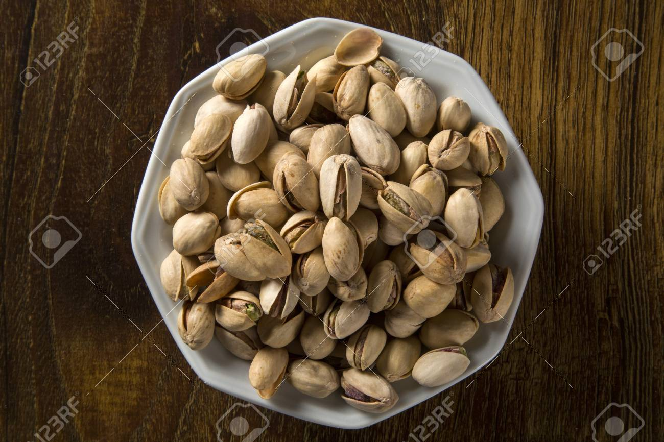 pistachio nuts in white bowl with wood background. - 78937018