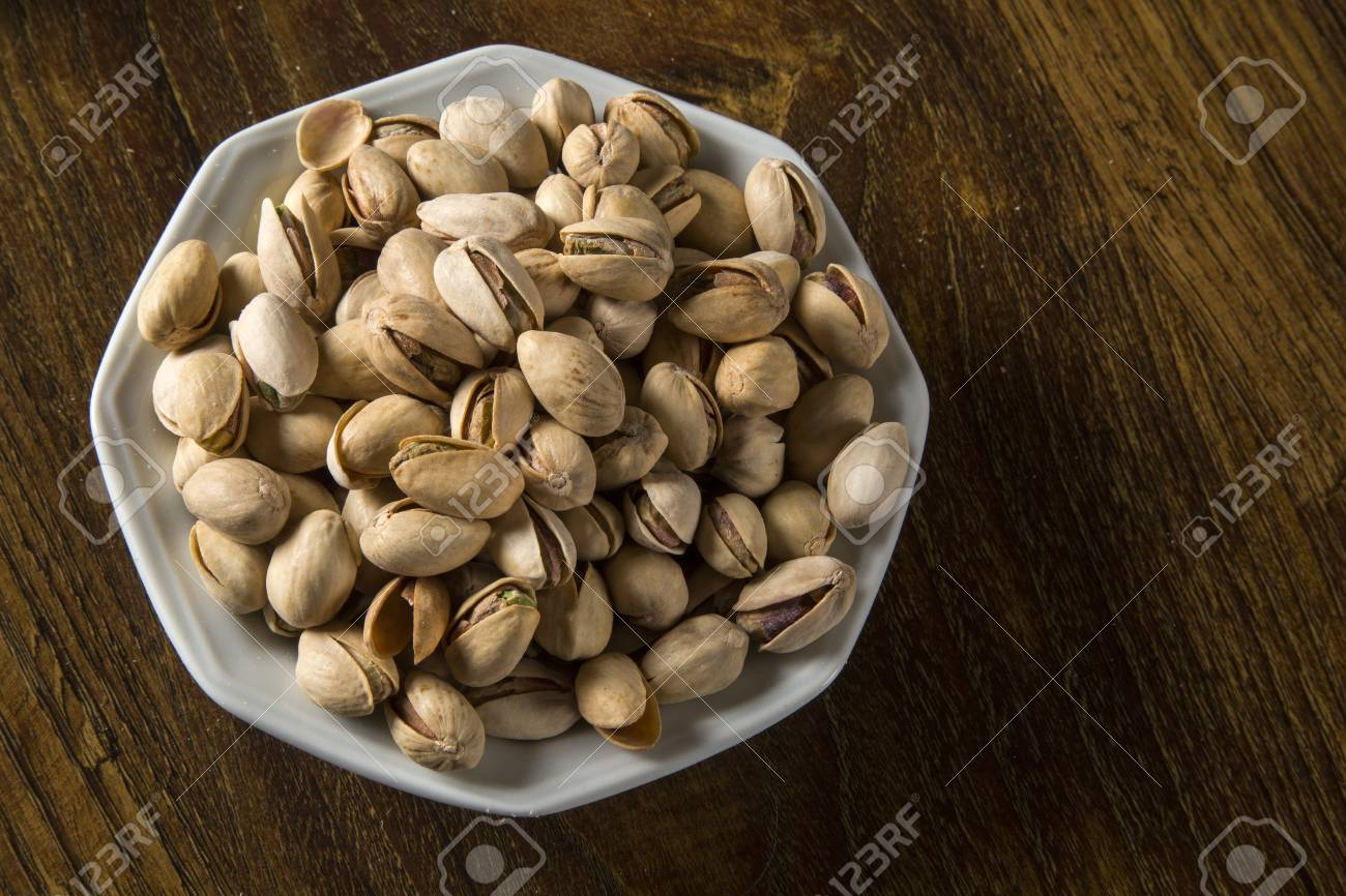 pistachio nuts in white bowl with wood background. - 79008458