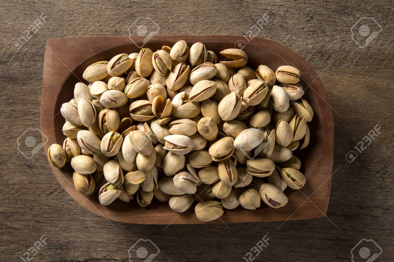 pistachio nuts in wood bowl with wood background. - 78949845