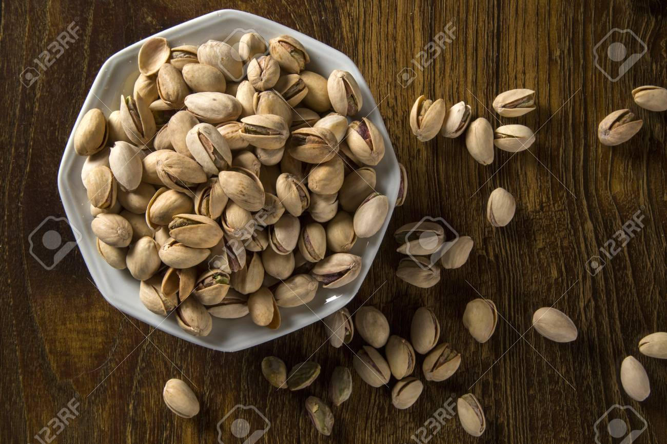 pistachio nuts in white bowl with wood background. - 79007930