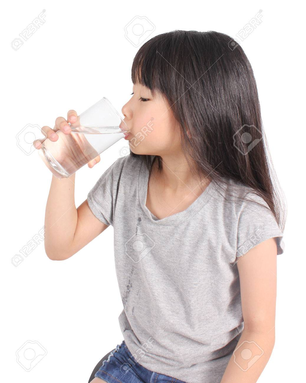 Young little girl drinking water. - 51687436