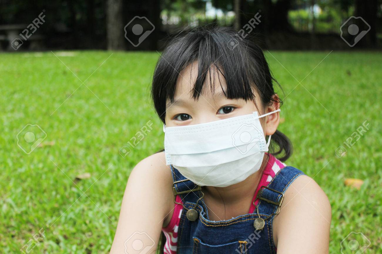Girl have a fever and wear protection mask with green grass background. - 71318604