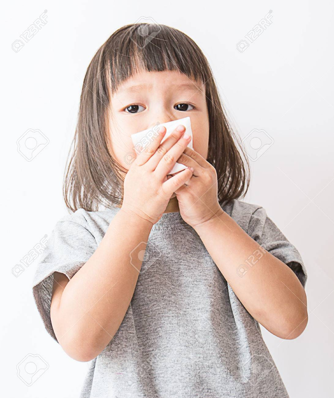 Cute little asian girl blows her nose over white background (asian) - 83058147