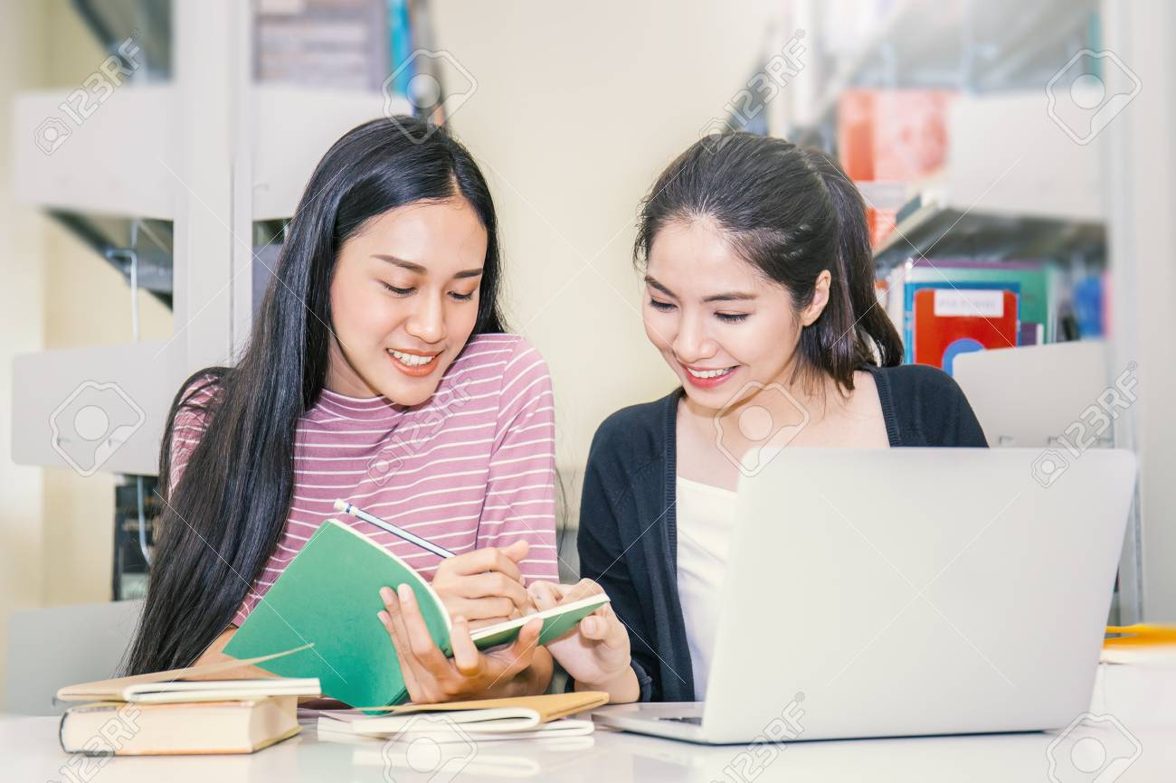 Two asian woman reading book at the library - Asian students sitting in school building reading book together. Education concept - 87173810