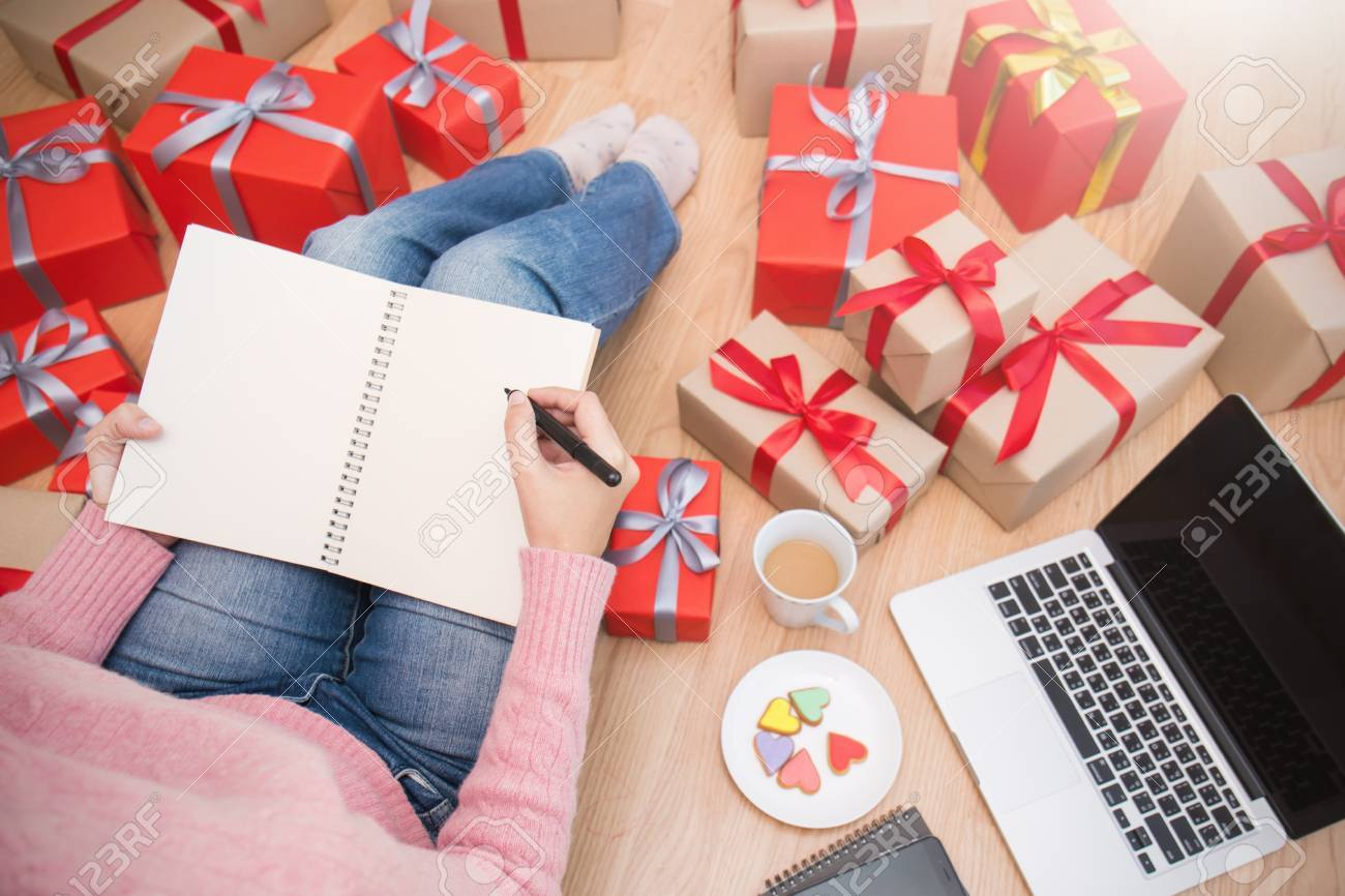 Hands holding pen whiting on notebook making gift list with Christmas gift box top view, Celebrate Christmas holiday online shopping background and banner concept. - 89708751