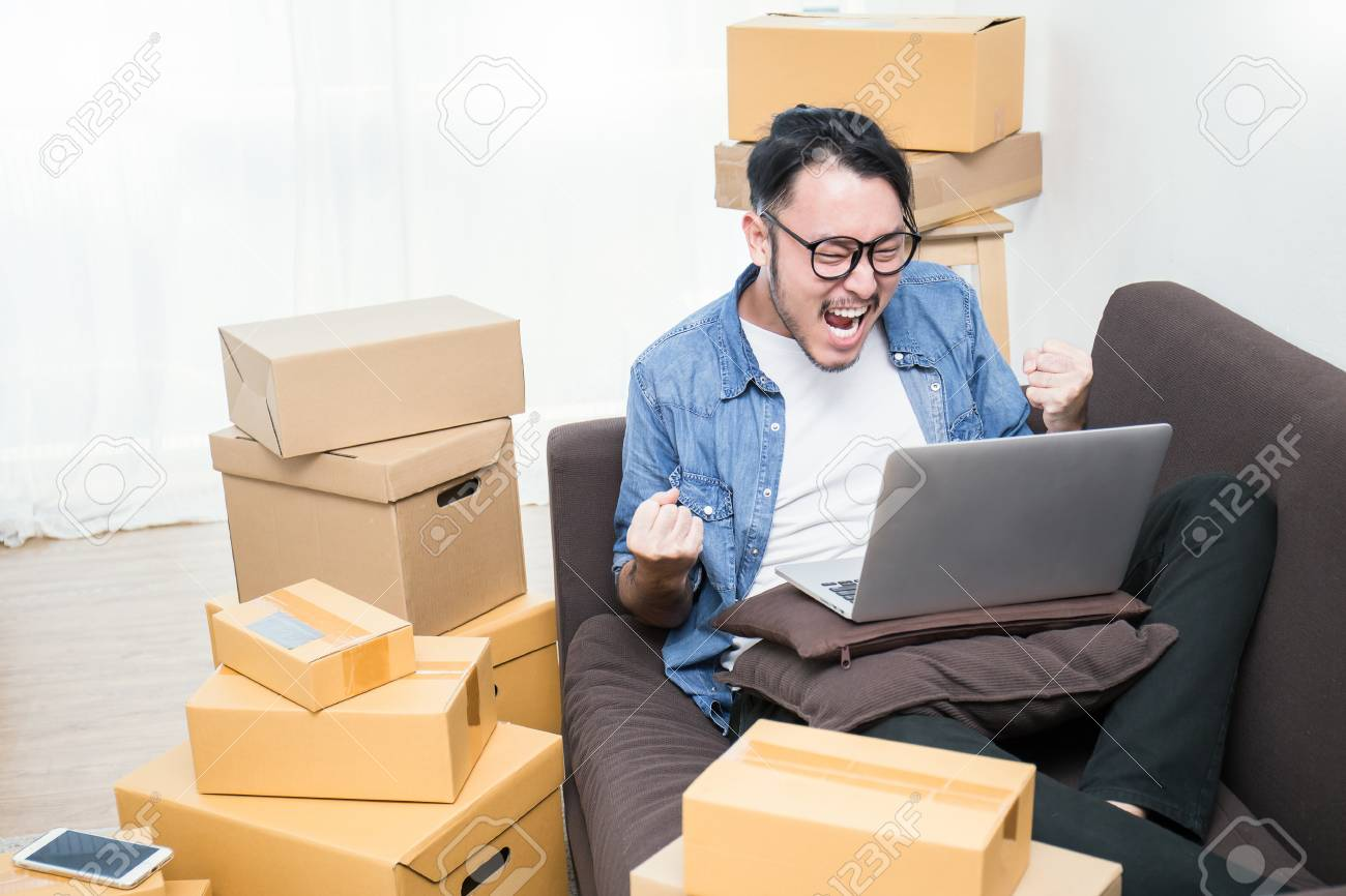 Start up small business entrepreneur SME or freelance asian man typing computer with box, Young happy success Asian man with his hand lift up , online marketing packaging box and delivery, SME concept - 90446342