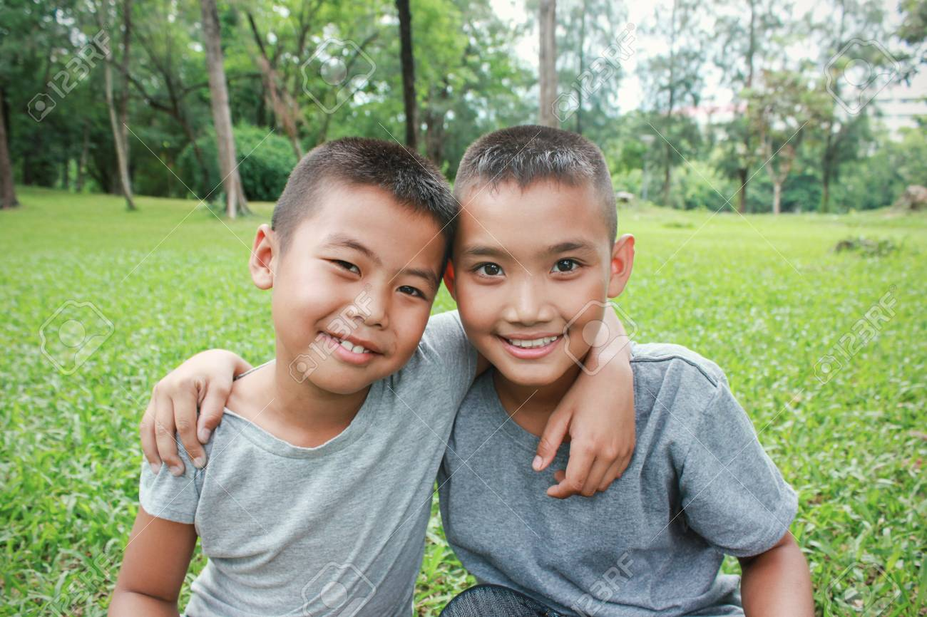 Portrait of young happy asian boys with green grass background, two  brothers having good time