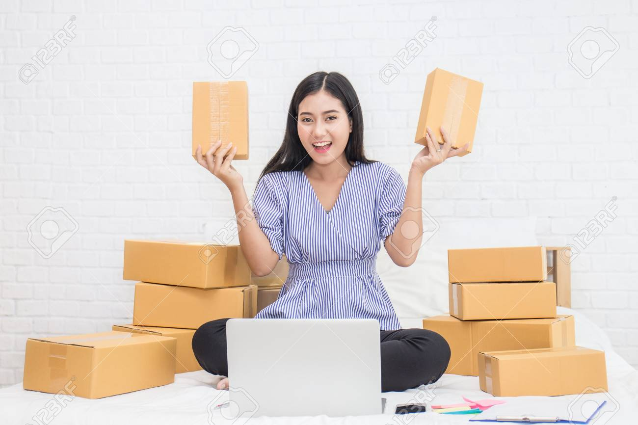 Start up small business entrepreneur SME or freelance woman holding boxes working at home concept, Young Asian small business owner at home office, on line marketing packaging and delivery, SME concept - 91205676
