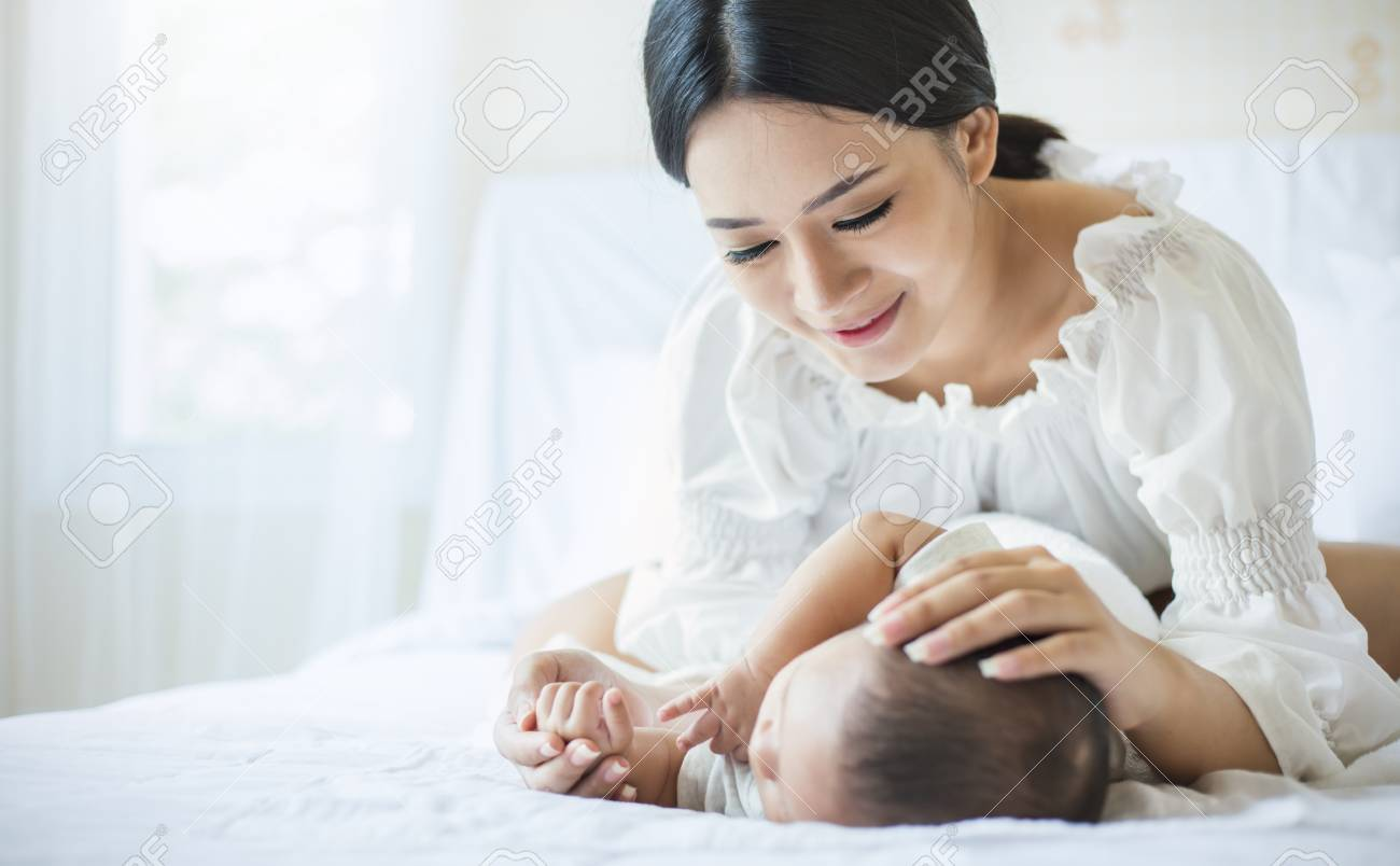 Close up portrait of beautiful young asian mother with her newborn baby, copy space with bed in the hospital background. Healthcare and medical love, lifestyle concept - 100942953