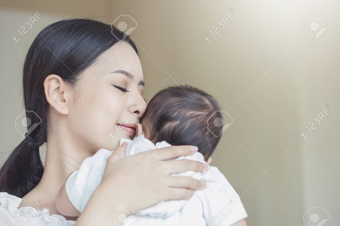 Close up portrait of beautiful young asian mother kissing her newborn baby. Healthcare and medical love lifestyle mother's day concept - 100941828