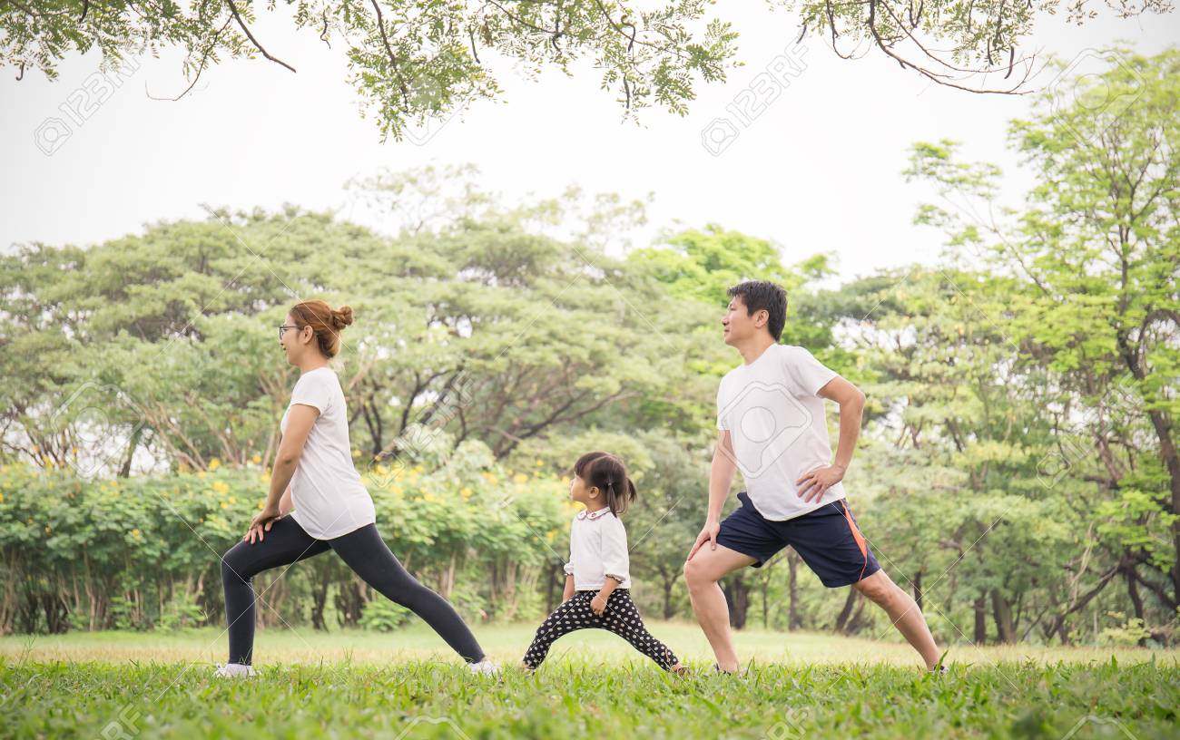 Family exercising and jogging together at the park. Group of family father mother and daughter stretching after sport on the grass. Sport health care and medical concept. - 112506970