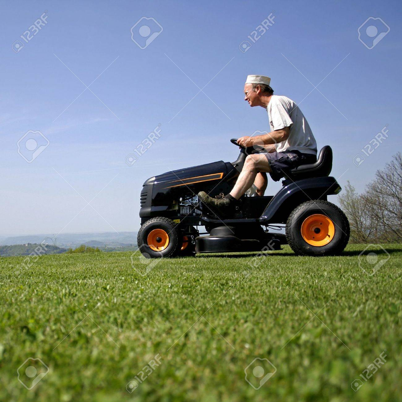 man sitting on a lawnmower in his garden Stock Photo - 4183097
