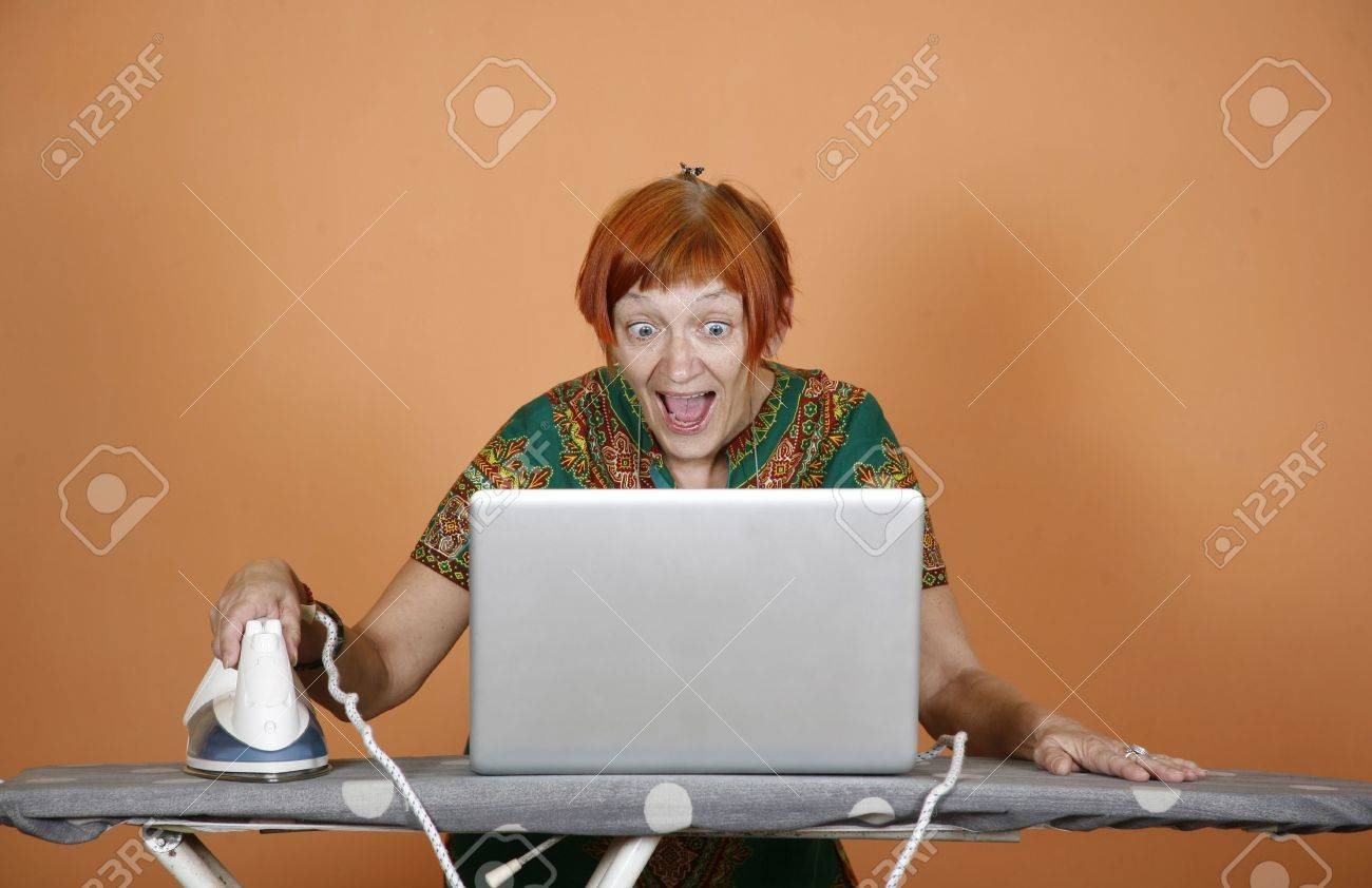 woman surfing the internet on her laptop and iron with surprise