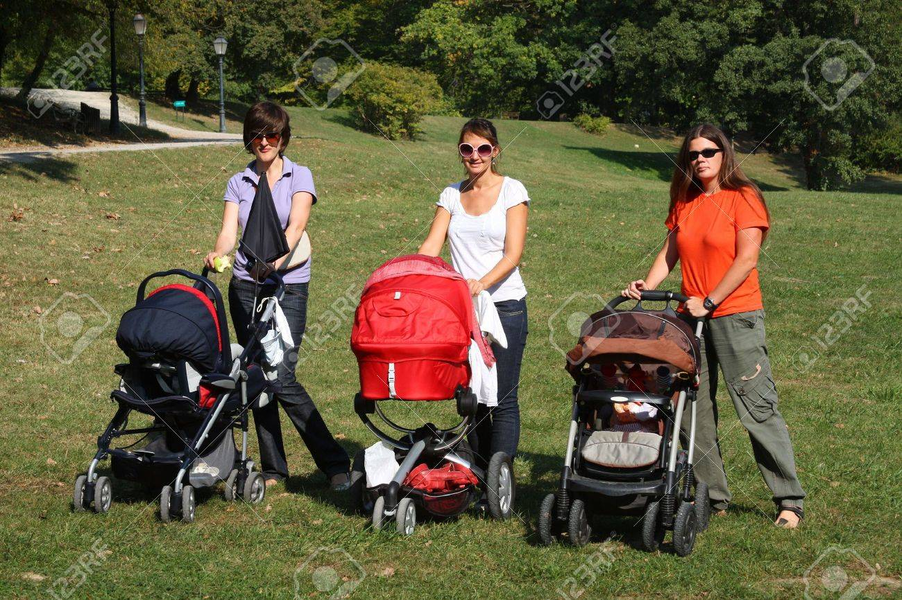 Mothers pushing their prams through the park in summer Stock Photo - 5901483