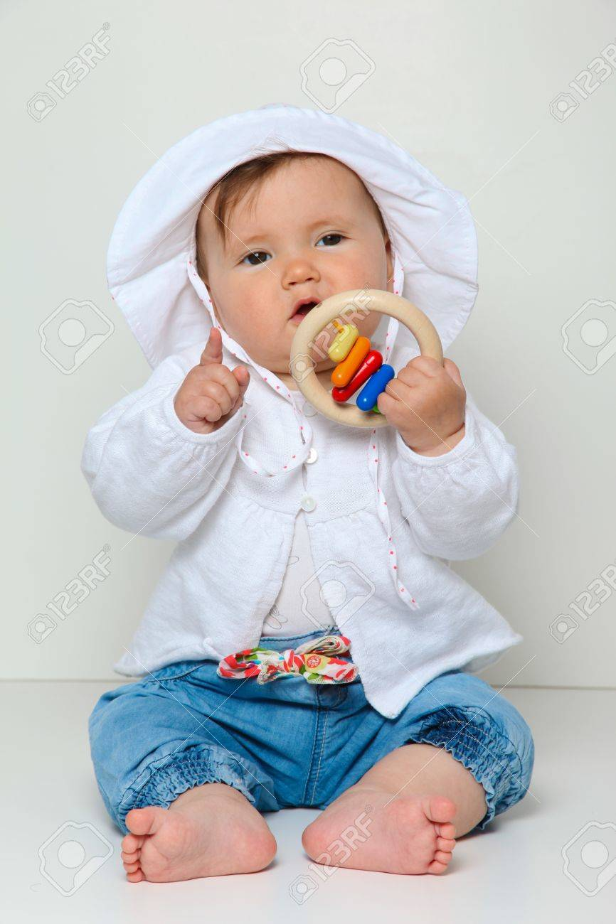 7 Month Old Baby Sitting With Toy Dressed In Jeans And Jumper ...