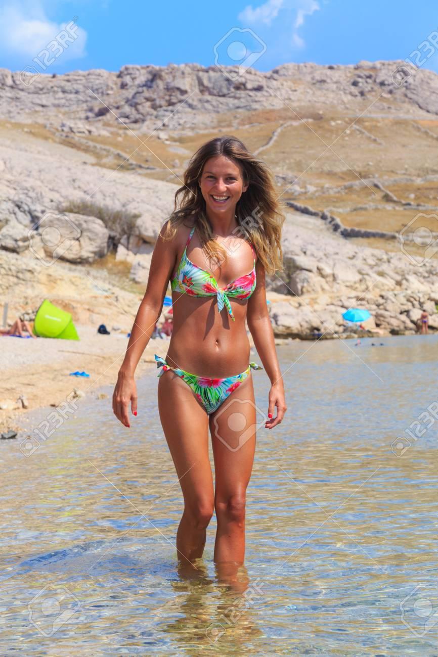 Beautiful Tanned Girl In A Bikini Standing In A Water Stock Photo 70770628