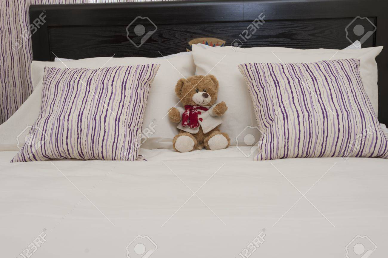 orsacchiotto e cuscini su un letto in una camera da letto dell ... - Cuscini Camera Da Letto