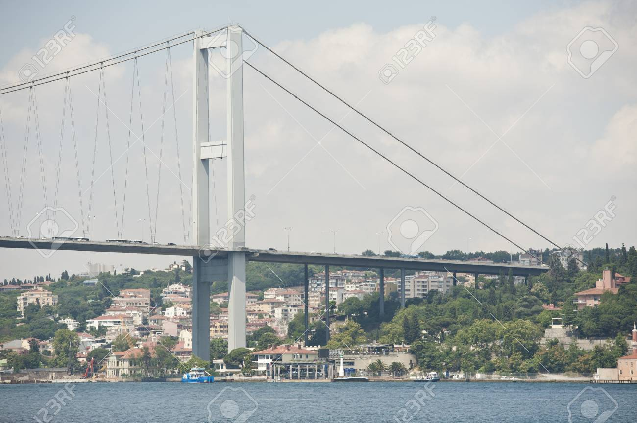 Large suspension road bridge over a river against a blue sky background with residences underneath Stock Photo - 23013082