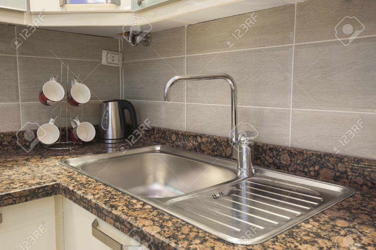 Kitchen Sink With Tap On Marble Counter And Kettle Next To Mug ...