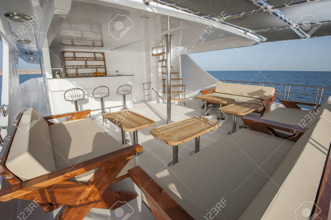 Rear Sundeck Of A Large Luxury Motor Yacht With Chairs Sofa Table And  Tropical Sea View