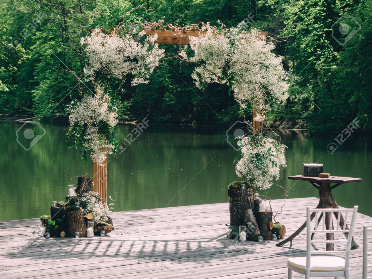 romantic rustic wedding ceremony near river white wooden chairs