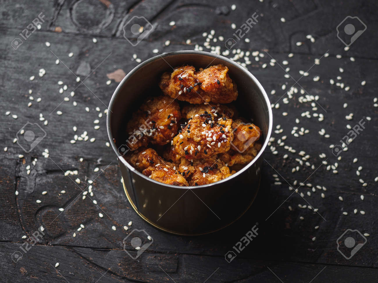 Breaded chicken meat pieces in metal can on black wood. - 169425542
