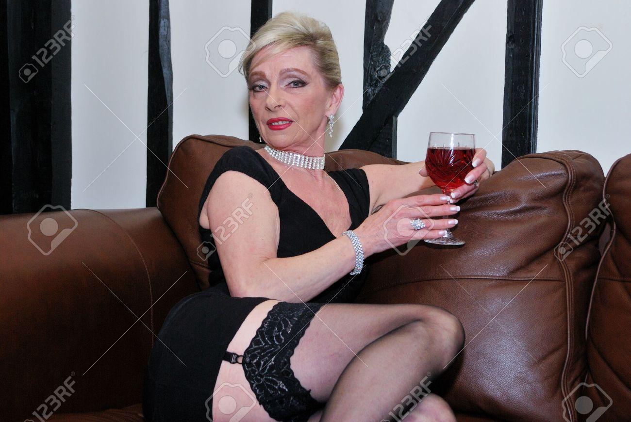 Banque d'images — grave femme mature en bas noirs assis sur fond blanc en regardant la caméra