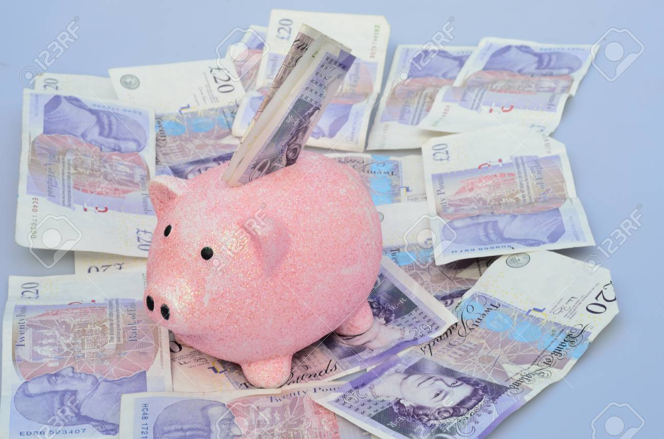 Pig over Money with some in slot Stock Photo - 22126781