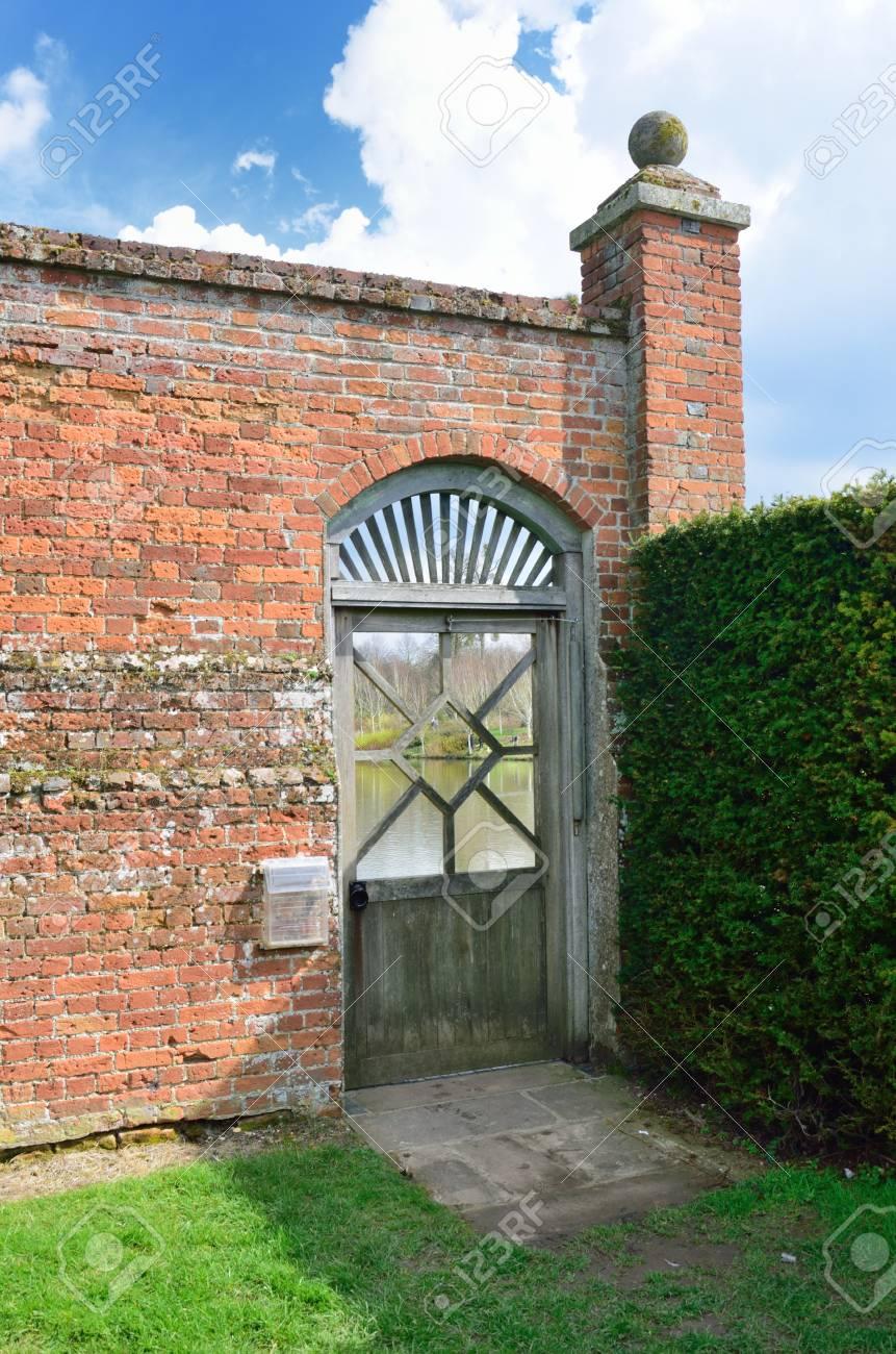 Porte de jardin en bois avec mur de briques rouges