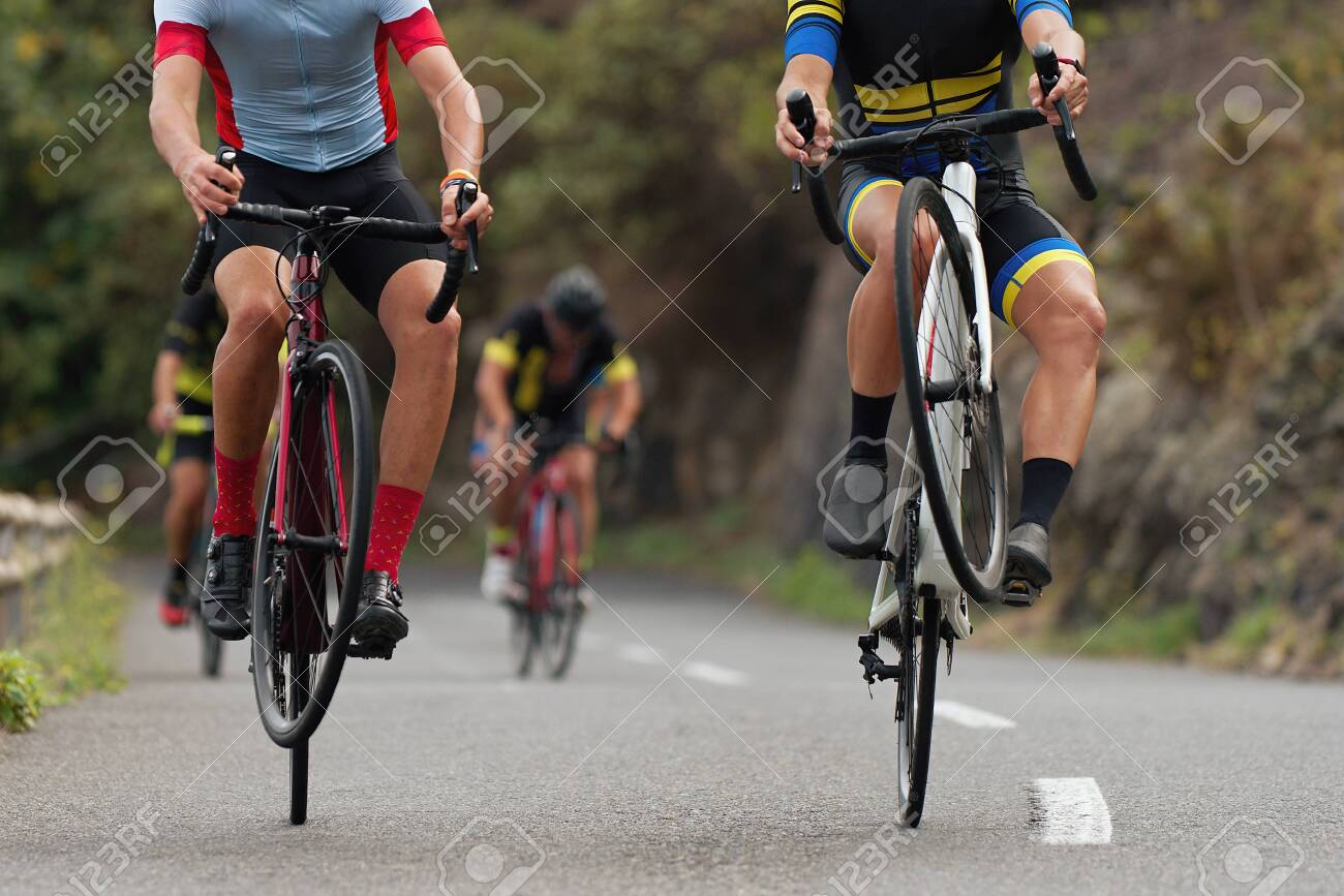 Cyclists riding on the rear wheel at the race. Balancing while driving on a road bike. Risky ride on one wheel - 132040392